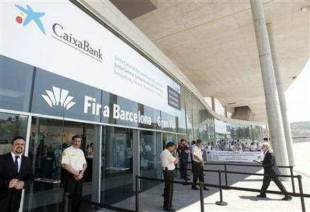 People protest at the entrance of Caixabank's extraordinary general shareholders meeting, where the approval of the decision for the merger of the bank by absorbing Banca Civica will be made, in Barcelona June 26, 2012. Like Spain's two largest banks Santander and BBVA , banking group La Caixa does not need external aid, but analysts and sources said it was just a matter of time before the Catalan powerhouse also unwinds stakes. REUTERS/Albert Gea