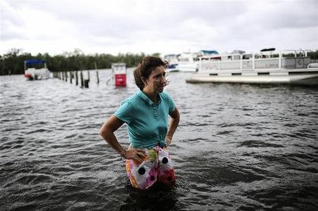 Doreen Mylin, owner of the Magic Manatee Marina, pauses to inspect the damage as the water associated with Tropical Storm Debby rises and floods her business in Homosassa, Florida, June 26, 2012.  REUTERS/Brian Blanco