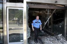 <p>Un guardia de seguridad camina entre los restos quemados de la entrada de las oficinas de Microsoft en Atenas, jun 27 2012. Hombres armados impactaron una camioneta llena de balones de gas contra la sede de Microsoft en Atenas y luego incendiaron el vehículo, causando importantes daños pero ningún herido, dijo el miércoles la policía. REUTERS/John Kolesidis</p>