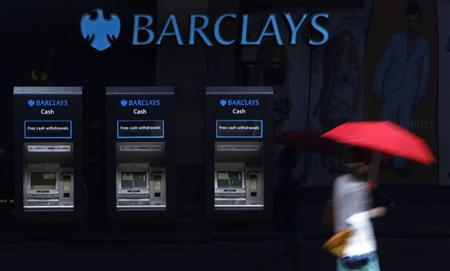 A woman walks past a line of Barclays cash dispensers in central London, June 27 2012. REUTERS/Andrew Winning