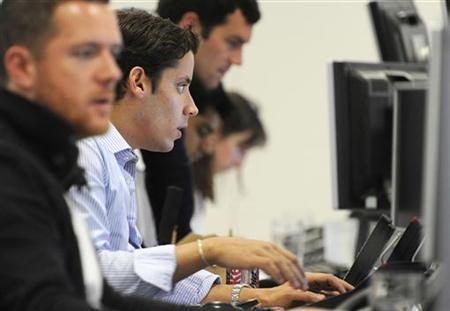 Traders check screen data at the IG Index trading floor in London June 11, 2012. REUTERS/Paul Hackett