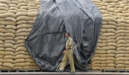 A security guard patrols beside stacked wheat sacks at a wholesale grain market in the northern Indian city of Chandigarh in this June 7, 2012 file photo. REUTERS/Ajay Verma/Files