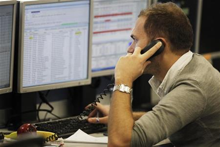 A trader holds a phone while checking screen data at the IG Index trading floor in London, December 9, 2011. REUTERS/Finbarr O'Reilly