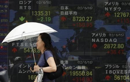 A woman carrying an umbrella passes an electronic board displaying a rise in Japan's Nikkei share average (top C), along with other global market indices, outside a brokerage in Tokyo June 18, 2012. REUTERS/Yuriko Nakao