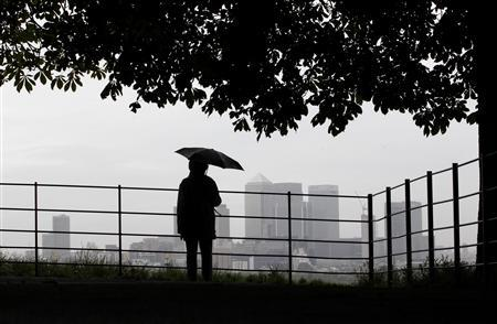 A man holds an umbrella as he looks out at London's Canary Wharf financial district from Greenwich park, July 2, 2012. Local media have reported that the government is expected to announce an independent inquiry into the future operation of Libor, but will stop short of setting up a full scale Leveson-style investigation into banking culture and practices. REUTERS/Andrew Winning