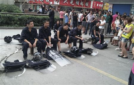 Riot police (L) sit next to local residents as they take a rest during a protest in Shifang, Sichuan province July 3, 2012. Residents in Shifang, a city in southwest China, took to the streets for a third day on Tuesday, demanding the government scrap plans for a copper alloy project they fear will poison them, in the latest unrest spurred by environmental concerns. REUTERS/Stringer