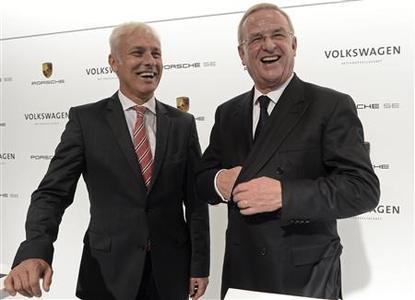 Martin Winterkorn, CEO of German carmaker Volkswagen (R) and CEO of Porsche, Matthias Mueller (L) laugh before a news conference in Wolfsburg, July 5, 2012. REUTERS/Fabian Bimmer