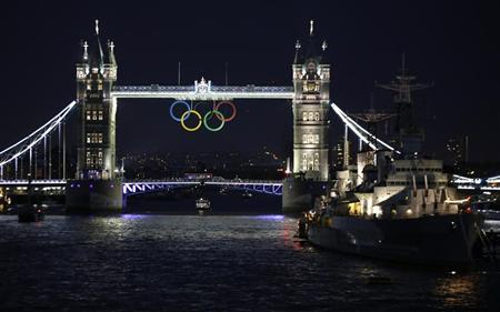 The Olympic rings are illuminated while suspended from Tower Bridge, near the HMS Belfast museum warship, as organisers marked one month to go until the London 2012 Olympic Games in London June 27, 2012. REUTERS/Chris Helgren