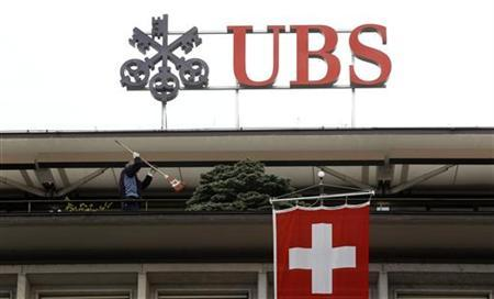 A Switzerland national flag flies in front of the logo of Swiss bank UBS at the company's headquarters in Zurich April 13, 2012. REUTERS/Arnd Wiegmann