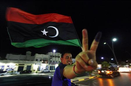 A man, with an inked finger, flashes the victory sign as he celebrates with the new Libyan flag at the end of voting day in Sirte July 7, 2012. Libyans defied violence and boycott calls to rush to the polls in their first free national election in 60 years on Saturday, parting with the legacy of Muammar Gaddafi's dictatorship. REUTERS/Anis Mili