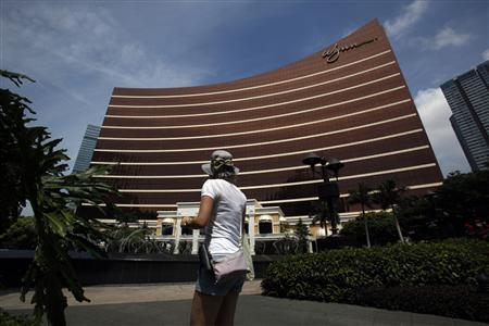 A visitor walks in front of the Wynn Macau resort in Macau June 5, 2012. The shadowy companies that bring China's millionaires to the gambling tables of Macau are facing their toughest time since the 2008 collapse of Lehman Brothers, and some of the smaller players may soon drop out of the game for good. These junket operators, who extend credit to rich gamblers and then collect any debts in exchange for a hefty commission, bring in about 70 percent of gambling revenue in Macau, the world's most profitable gaming destination. The health of the junket industry is critical for Macau's casinos, including those owned by U.S. gambling titans - Sheldon Adelson's Sands China and Steve Wynn's Wynn Macau. Picture taken June 5, 2012. REUTERS/Bobby Yip
