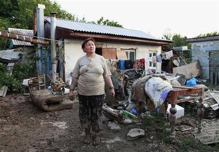 A woman stands in a courtyard of her house, hit by floods, in the town of Krymsk in Krasnodar region, southern Russia, July 8, 2012. The Russian President has ordered an investigation into accusations that officials could have done more to prevent floods killing at least 150 people in southern Russia, hoping to limit the criticism that has followed earlier disasters. REUTERS/Eduard Korniyenko