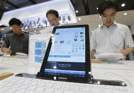 People try out the Galaxy Tab 10.1 displayed in a store at the headquarters of Samsung Electronics in Seoul July 6, 2012. REUTERS/Lee Jae-Won