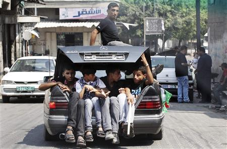 Palestinians sit in the boot of a car as they follow the convoy of released Palestinian soccer player Mahmoud Al-Sarsak (not pictured) upon his arrival in Gaza City July 10, 2012. Israel released the Gaza soccer player on Tuesday in a deal to end his intermittent four-month hunger strike after he spent three years behind bars without being put on trial, officials said. Picture taken through a car window. REUTERS/Mohammed Salem