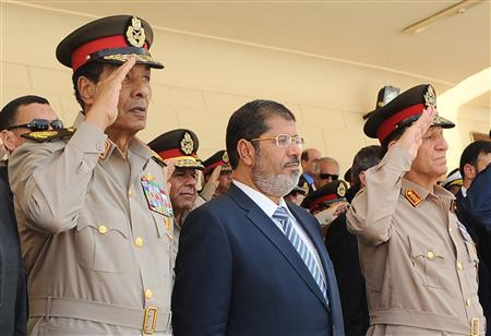 Egypt's President Mohamed Mursi (C), head of the military council Field Marshal Hussein Tantawi (L) and Egyptian armed forces Chief of Staff Sami Anan (R) attend a graduation ceremony for air forces cadets in Sharquiya, 65 km northeast of Cairo, July 10, 2012. REUTERS/Egyptian Presidency/Handout