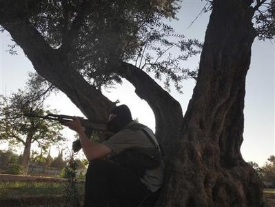 A member of the Free Syrian Army sits near a tree in Damascus July 9, 2012. Picture taken July 9, 2012. REUTERS/Shaam News Network/Handout