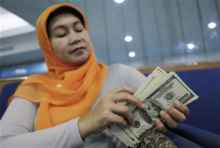 A woman counts her U.S. dollar bills at a money changer in Jakarta June 13, 2012. REUTERS/Beawiharta