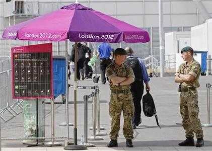Soldiers man a security checkpoint at an entrance to the London 2012 Olympic Park at Stratford in London July 12, 2012. Britain's interior minister had to answer questions in parliament on Thursday after admitting that she was putting extra troops on standby for Olympic security, just two weeks before the London Games begin, because a private contractor might not meet its commitments. REUTERS/Luke MacGregor