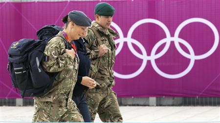 Members of the armed forces walk past the Olympic rings on the perimeter of the Olympic Park in Stratford, the location of the London 2012 Olympic Games, in east London July 15, 2012. The head of private security firm G4S said on Saturday his firm only realised just over a week ago it would not be able to supply enough venue guards for this month's London Olympics, as he publicly apologised for the embarrassing failure. On Thursday, the government said it would deploy additional troops after it became clear G4S was unlikely to provide the expected 10,400 guards it was contracted to do because of problems processing applicants. REUTERS/Andrew Winning