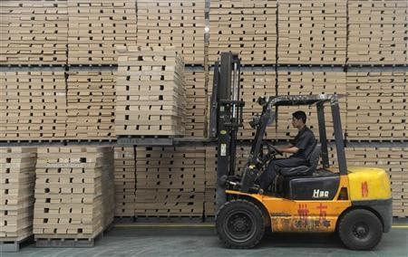 A worker operates a forklift to transport floor boards at a wood flooring factory in Huzhou, Zhejiang province July 13, 2012. REUTERS/Sean Yong