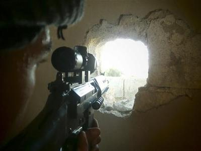 A member of the Free Syrian Army points his weapon through a hole in a wall as he takes up a defense position in a house in Qusseer neighbourhood in Homs July 16, 2012. Picture taken July 16, 2012. REUTERS/Shaam News Network/Handout