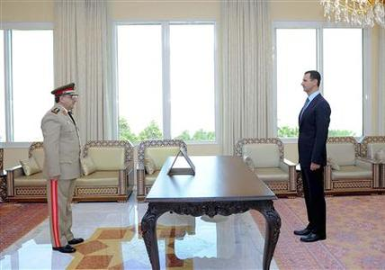 Daoud Rajha is sworn in as Deputy Prime Minister and Defense Minister by Syrian President Bashar al-Assad (R) in Damascus in this October 9, 2011 file photo. Rajha was killed by a bomb which exploded during a meeting of ministers and security officials at a national security building in Damascus on July 18, 2012, state television said. Picture taken October 9, 2011. REUTERS/SANA/Files
