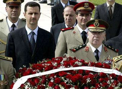 Syrian President Bashar al-Assad (C) and former Defence Minister Hassan Turkmani (R) attend a ceremony in Damascus, in this file photo taken this May 6, 2004. REUTERS/Sana/Files