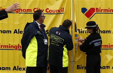Members of G4S security and a police officer open a gate at the Alexander Stadium in Birmingham, central England, July 18, 2012. REUTERS/Darren Staples