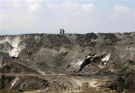 People walk on top of a mound of slag inside Sichuan Hongda's factory, where a new Hongda plant is due to be built in Shifang, Sichuan province, July 4, 2012. REUTERS/Petar Kujundzic