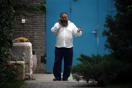 Chinese dissident artist Ai Weiwei talks on his mobile phone as he walks near the entrance to his studio in Beijing June 20, 2012. REUTERS/David Gray