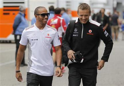 McLaren Formula One driver Lewis Hamilton (L) of Britain arrives with a team member ahead of the German F1 Grand Prix at the Hockenheim circuit July 19, 2012. REUTERS/Alex Domanski