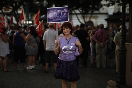 Isabel Marin, 60, who is unemployed, poses for a photograph holding a placard that reads: ''Not one step back in equality policies'' as she takes part in a protest march against austerity measures in Malaga, southern Spain, July 19, 2012. REUTERS/Jon Nazca