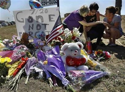 Isaac Pacheco (C) is comforted after leaving a birthday card for his friend Alex Sullivan, who was killed in the Denver-area movie killings, at a memorial site for victims behind the theater where a gunman opened fire on moviegoers in Aurora, Colorado July 21, 2012. REUTERS/Shannon Stapleton