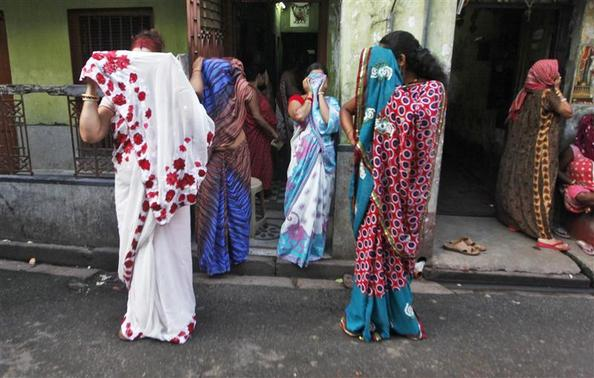 Sex workers cover their faces as they react to the camera while watching a rally as part of the week-long sex workers' freedom festival at the Sonagachi red-light area in Kolkata July 24, 2012. REUTERS/Rupak De Chowdhuri