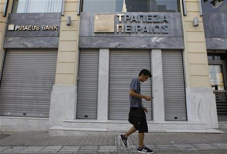 A man walks outside of a closed Piraeus bank branch in central Athens July 16, 2012. Greece's Piraeus Bank on Monday confirmed it was interested in buying struggling state-controlled ATEbank, as the country's battered banking sector looks to consolidate to weather a debilitating debt crisis. REUTERS/John Kolesidis
