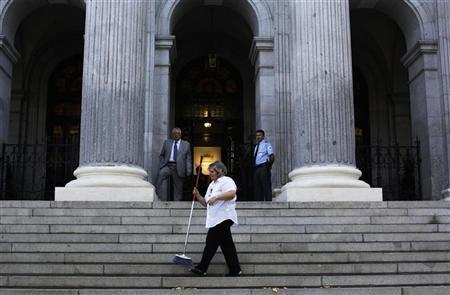 A worker sweeps outside Madrid's Bourse July 23, 2012. REUTERS/Susana Vera