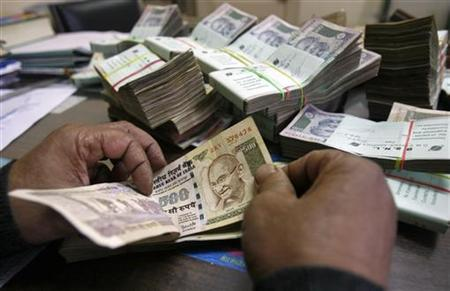 An employee counts Indian rupee notes at a cash counter inside a bank in Agartala, capital of India's northeastern state of Tripura December 31, 2010. REUTERS/Jayanta Dey