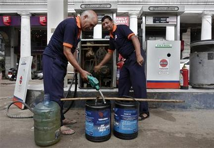 Employees manually fill containers with diesel during a power cut at a fuel station in New Delhi July 31, 2012. REUTERS/Adnan Abidi