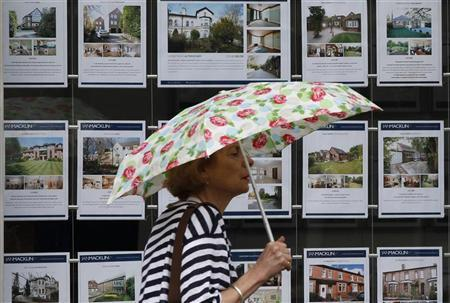 A woman holds an umbrella as she walks past the window of an estate agents office in Manchester, northern England June 7, 2011. REUTERS/Phil Noble
