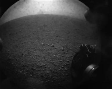 In this image from NASA TV, shot off a video screen, one of the first images from the Curiosity rover is pictured of its wheel after it successfully landed on Mars. REUTERS/Courtesy NASA TV/Handout