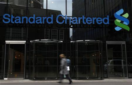 A woman walks past a Standard Chartered bank in London October 13, 2010. REUTERS/Stefan Wermuth