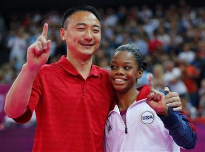 Gabrielle Douglas (R) of the U.S. is seen with her coach Liang Chow before competing in the women's gymnastics balance beam final in the North Greenwich Arena during the London 2012 Olympic Games August 7, 2012. REUTERS/Mike Blake