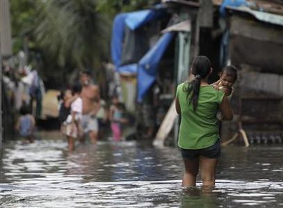 A resident carrying a child wades through floodwaters brought about by monsoon rains in Navotas, Metro Manila August 9, 2012. REUTERS/John Javellana