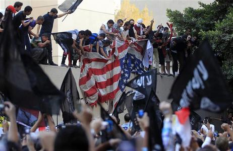 Protesters destroy an American flag pulled down from the U.S. embassy in Cairo September 11, 2012. Egyptian protesters scaled the walls of the U.S. embassy, tore down the American flag and burned it during a protest over what they said was a film being produced in the United States that insulted Prophet Mohammad. REUTERS/Mohamed Abd El Ghany