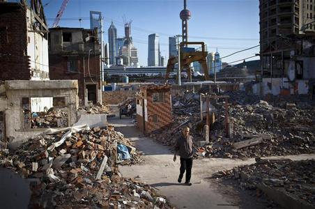 A resident holds a spittoon as he walks in an area where old residential buildings are being demolished to make room for new skyscrapers in central Shanghai, October 17, 2012. REUTER/Aly Song