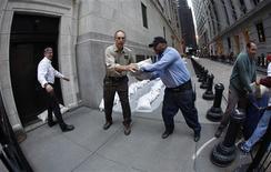 <p>Des employés de Wall Street installent des sacs de sable devant les portes et sur les bouches d'aération. La Bourse de New York restera fermée lundi et peut-être aussi mardi alors que l'ouragan Sandy doit aborder dans les heures à venir la côte Est des Etats-Unis. /Photo prise le 28 octobre 2012/REUTERS/Carlo Allegri</p>