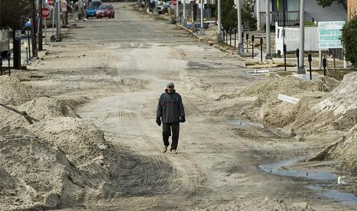 A resident walks through plowed beach sand three days after Hurricane Sandy came ashore in Seaside Heights, New Jersey, November 1, 2012.  REUTERS/Steve Nesius