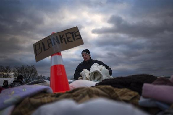 A victim of hurricane Sandy takes blankets from a aid distribution site in the Staten Island borough of New York November 3, 2012. REUTERS-Adrees Latif