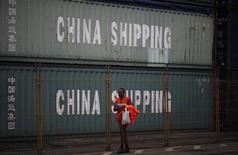 <p>Imagen de archivo de un trabajador junto a una serie de contenedores de China Shipping en el puerto de Santos, Brasil, sep 20 2012. Economistas recortaron su pronóstico de inflación en Brasil para este año, según un sondeo semanal del Banco Central, en una señal de que el salto en los precios de los alimentos comienza a debilitarse. REUTERS/Nacho Doce</p>