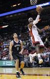 <p>Panier de LeBron James du Miami Heat sous le regard de Brook Lopez des Brooklyn Nets. Le Heat a remporté mercredi sa quatrième victoire d'affilée sur son parquet en humiliant les Nets 103-73 en match de la saison régulière de NBA. /Photo prise le 7 novembre 2012/REUTERS/Andrew Innerarity</p>